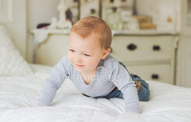 Cute blond Baby crawling on bed — Stock Photo