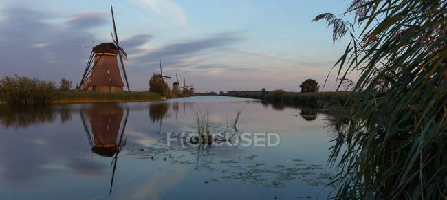 Живописный вид ветряные мельницы вдоль реки, Киндердейк, Нидерланды — стоковое фото