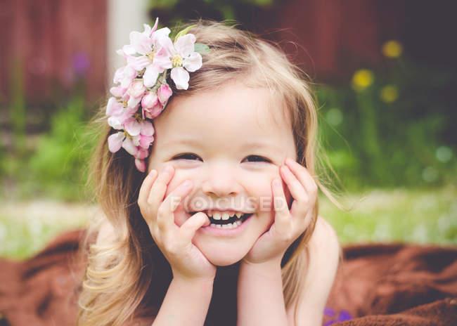 Сміючись дівчинка з квітами у волоссі, дивлячись на камеру — стокове фото