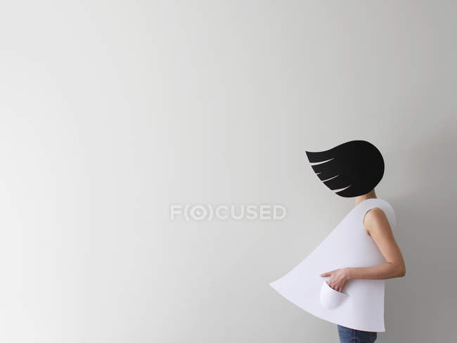 Conceptual woman wearing paper clothes and hair in wind standing in front of white background — Stock Photo