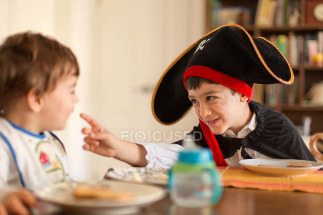 Boy dressed in pirate costume playing with toddler brother sitting at table — Stock Photo