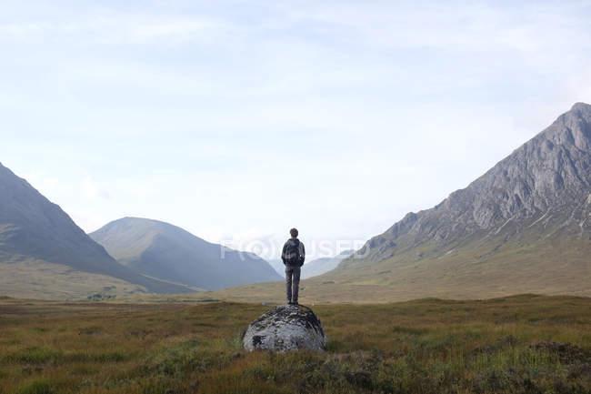 Homme debout sur le rocher et regardant la vue, Highlands, Écosse, Royaume-Uni — Photo de stock