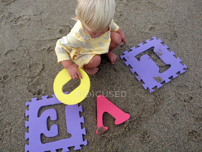 Blond little girl playing with colorful puzzle letters — Stock Photo