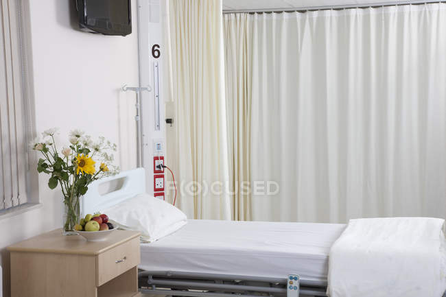 Empty hospital bed on hospital ward with flowers — Stockfoto