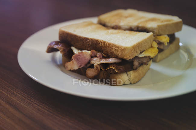 Tasty bacon and egg sandwiches on a plate — Stock Photo