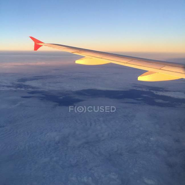 Airplane wing and sunset above the clouds — Stockfoto