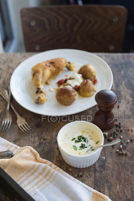 Frango e batatas com molho do assado sobre a mesa de madeira rústica — Fotografia de Stock