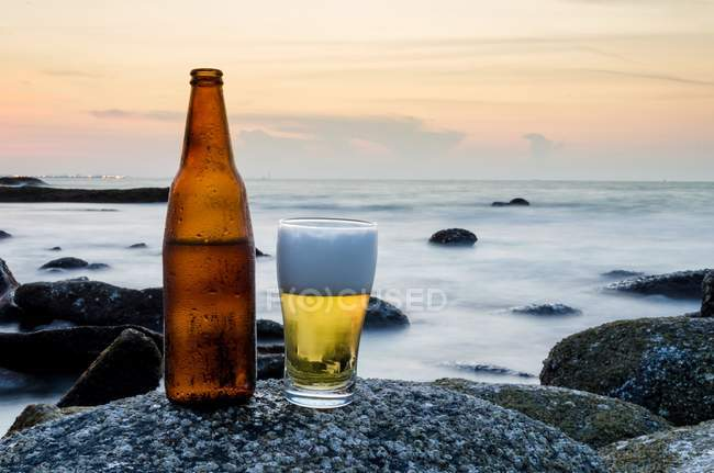 Glass of beer and bottle of beer on a rock on the beach — Stockfoto