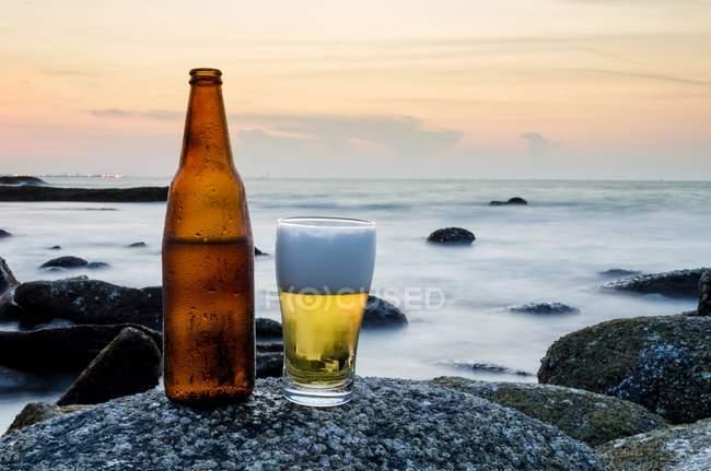 Glas Bier und eine Flasche Bier auf einem Felsen am Strand — Stockfoto