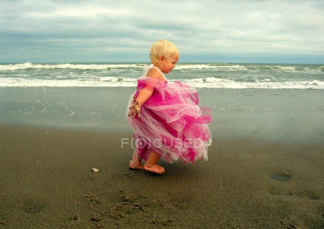 Fille qui porte la robe rose debout sur la plage de journée venteuse — Photo de stock