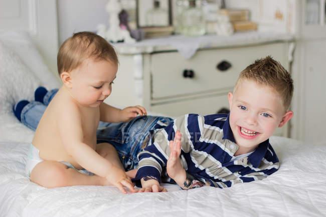 Mignons petits frères souriants jouant sur le lit — Photo de stock