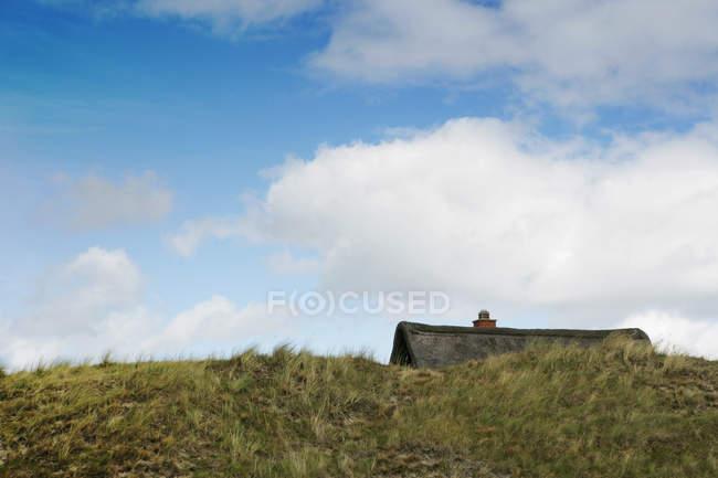 Techo del Summerhouse en Dinamarca estilo detrás colina de - foto de stock