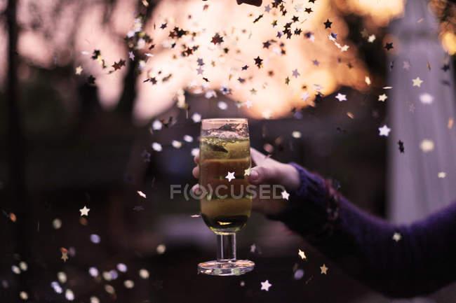Mano humana sosteniendo la Copa de champán con estrellas de papel, el concepto de la celebración del vuelo - foto de stock