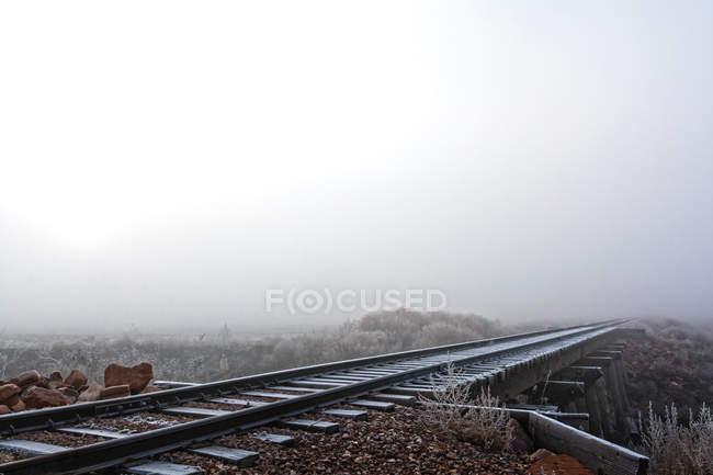 Мистический вид железнодорожных путей, исчезающих в тумане — стоковое фото