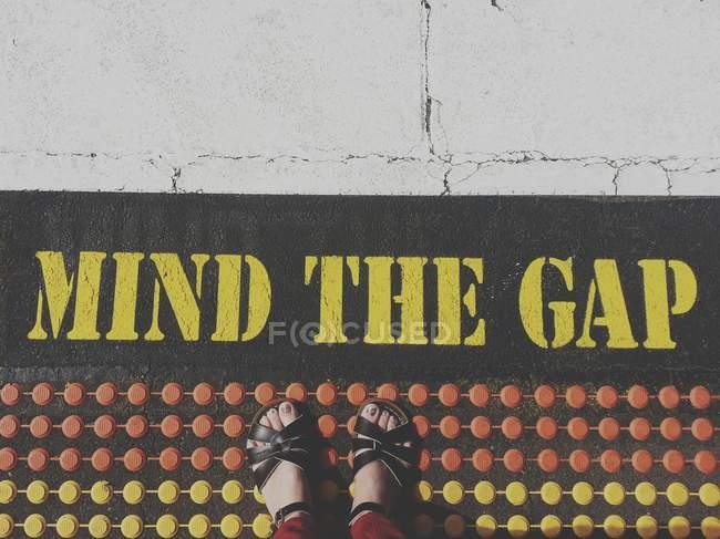 Blick nach unten auf weibliche Beine, die auf Asphalt stehen, mit Text, der die Lücke verdeutlicht — Stockfoto