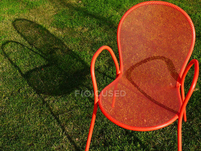 Closeup of orange chair in green grass — Stockfoto