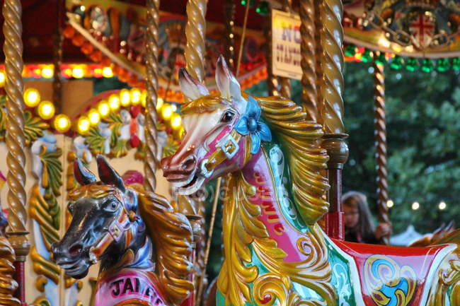 Closeup view of colorful carousel horses at amusement park — Stockfoto