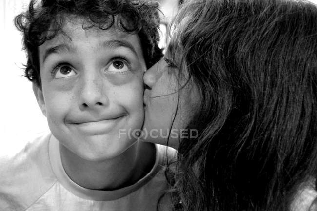 Close-up portrait of Girl kissing boy on the cheek — Stock Photo
