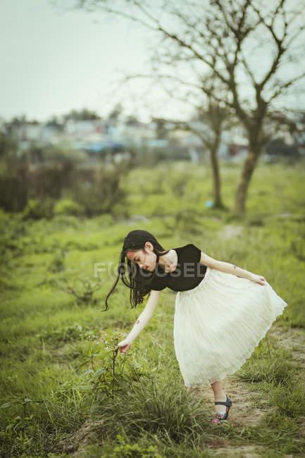 Menina vestindo vestido escolhendo plantas na natureza — Fotografia de Stock