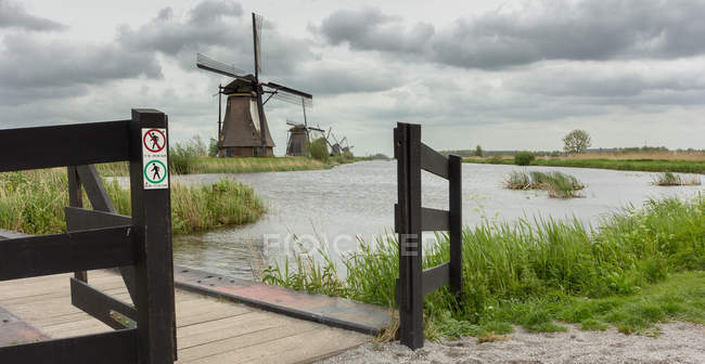 Scenic view of windmill along river, Kinderdijk, Netherlands — Stock Photo