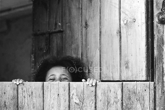 Menina se escondendo atrás de porta jogando esconder e procurar — Fotografia de Stock