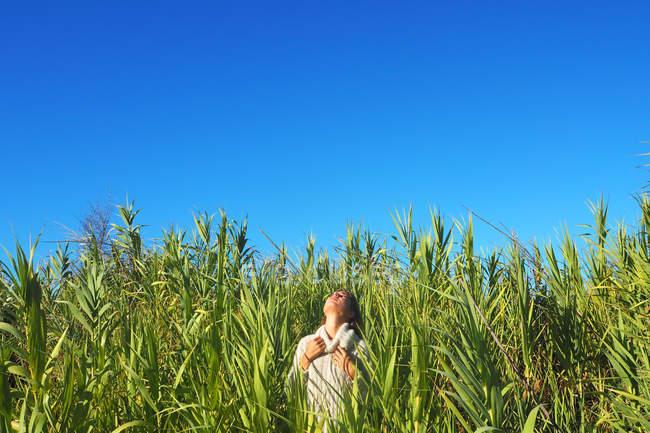 Donna in piedi in un campo con la testa indietro e le mani sul petto — Foto stock