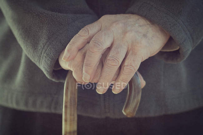 Close-up of male hands holding walking stick — Stock Photo
