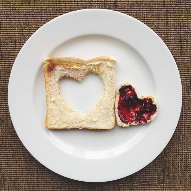 Heart in toast with jam on white plate — Stockfoto