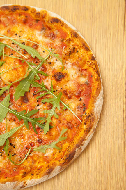 Close-up of vegetarian Pizza with arugula on wooden surface — Stockfoto