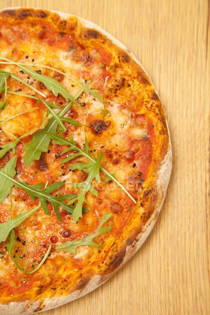 Vegetarische Pizza mit Rucola auf Holzoberfläche in Nahaufnahme — Stockfoto