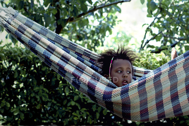 Portrait of cute little girl in hammock during summer day — Stock Photo