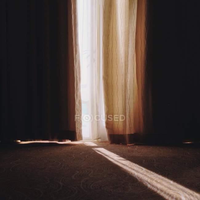 Sunbeam durchschimmern Lücke in Gardinen — Stockfoto