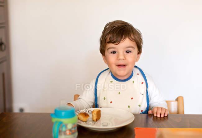Улыбающийся мальчик сидит за столом, есть снэк — стоковое фото