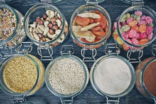 Reihen von Gläser gefüllt mit Samen, Nüssen, getrockneten Früchten und Süßigkeiten — Stockfoto
