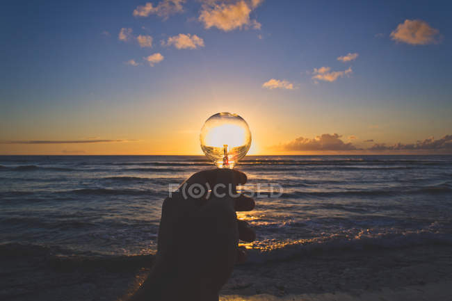 Scenic view of hand holding lightbulb at sunset — Stock Photo