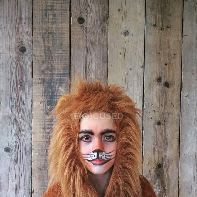 Adorable petite fille habillée en costume de lion sur fond en bois — Photo de stock