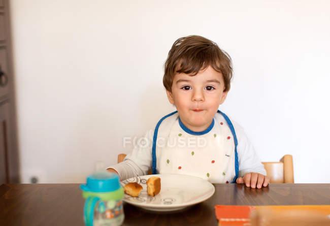Niedliche kleine freche Junge sitzt am Tisch und isst Snack — Stockfoto