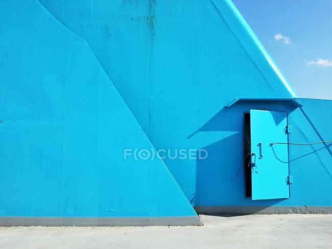 Pont bleu à bord du navire avec porte métallique et ciel bleu — Photo de stock