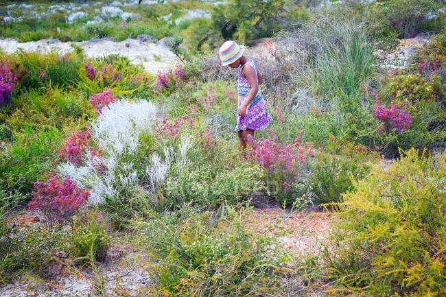 Girl walking through wildflowers in nature — Stock Photo