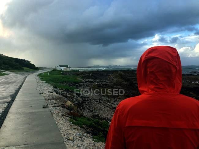 Homem vestindo jaqueta de chuva vermelha andando na costa — Fotografia de Stock