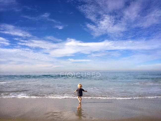 Блондинка маленький хлопчик працює на пляжі — стокове фото