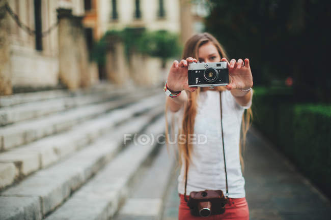 Молодая женщина держит ретро-камеру рядом с лестницей — стоковое фото