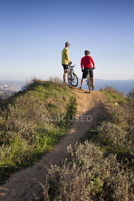 Two men standing with mountain bikes and looking at ocean — Stockfoto