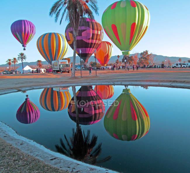 Hot Air Balloons reflected in pond at Lake Havasu Balloon Festival, Beachcomber Boulevard, Arizona, USA — Stock Photo