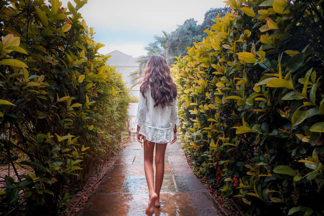 Rear View Of A Young Girl Walking Down A Path between green bushes — Stock Photo