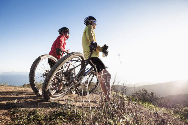 Two men leaning against mountain bikes in nature — Stock Photo