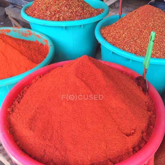 Blue buckets of ground chilli at market — Stockfoto