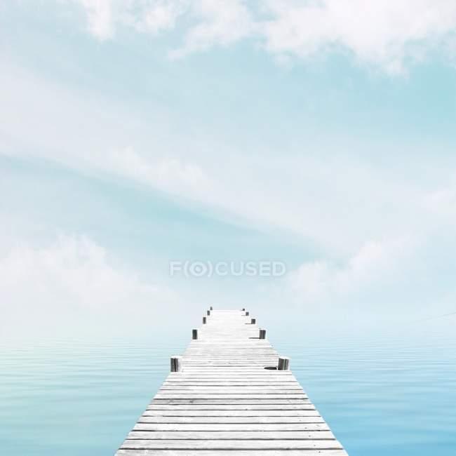 Holzsteg gegen Meer unter blauem Himmel — Stockfoto