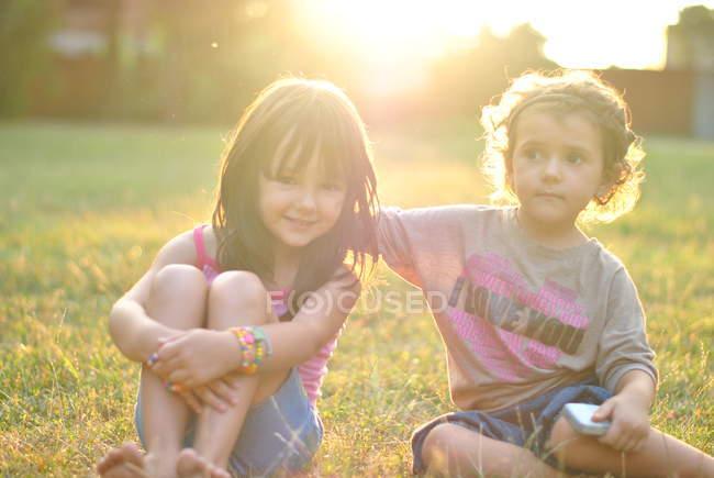 Две сестры счастливым, сидя на траве вместе, один холдинг смартфон — стоковое фото