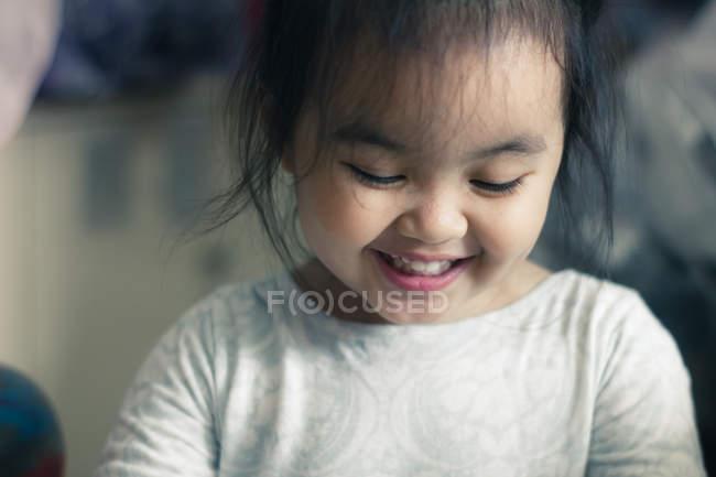 Улыбающаяся маленькая девочка смотрит вниз — стоковое фото
